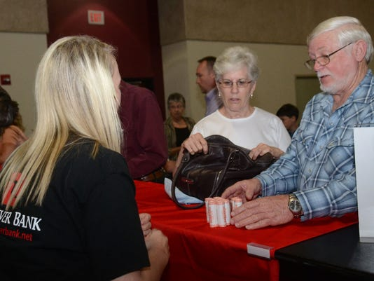 Peg Booty (center) and husband Dean Booty exchange for quarters featuring the Kisatchie National Forest at the official coin launch held Wednesday, April 22, 2015 at the Riverfront Center in downtown Alexandria. The Bootys are from the community of Kisatch