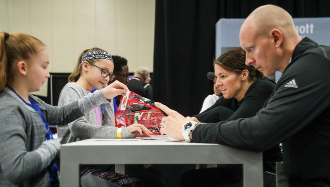 As Chris Mack works the phone, his family wait for him and play cards at the National Association of Basketball Coaches convention in San Antonio, Texas. Mack admits that for him 'sleep is overrated.'March 30, 2018.