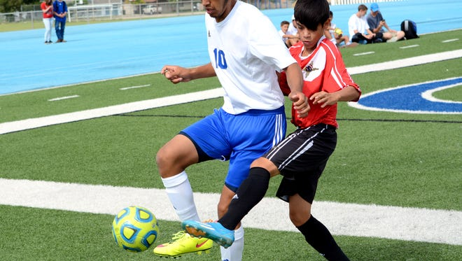 Carlsbad's Marco Aguilar keeps the ball inbounds against Centennial's Missael Torres in the first half Saturday.