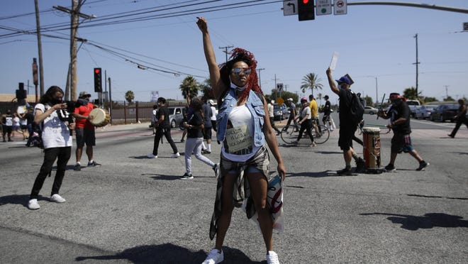 A protester raises her fist during a march in honor of Andres Guardado on Sunday, June 21, 2020, in Compton, Calif. Guardado was shot Thursday after Los Angeles County sheriff's deputies spotted him with a gun in front of a business near Gardena.