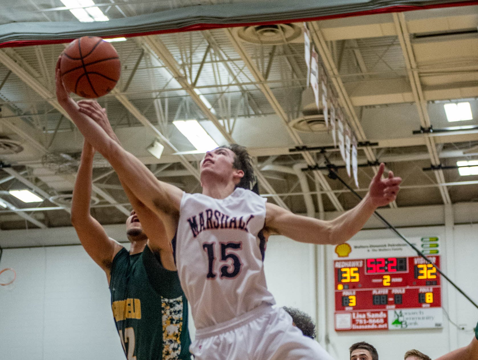 Marshall's T.J. Rocco (15) goes for the ball over Marshall defender at Friday evening,s game.