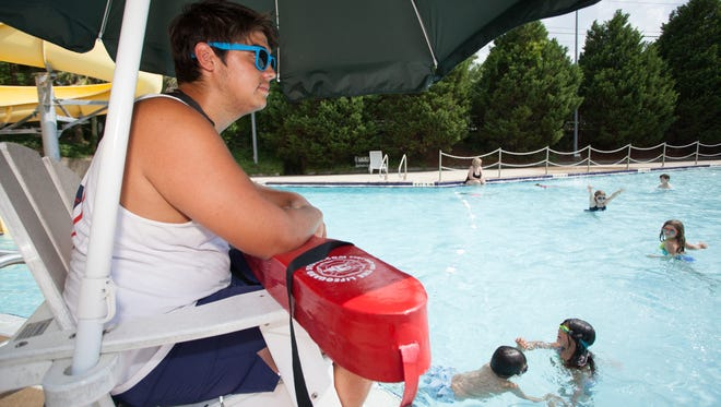Lifeguard Javier Vintimilla watches over children playing in a pool at the Trousdell Aquatics Center