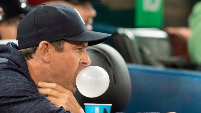 New York Yankees manager Aaron Boone blows a bubble with chewing gum in the sixth inning of a baseball game against the Toronto Blue Jays in Toronto, Friday, March 30, 2018.