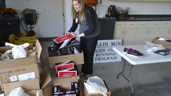 Tia DeLeers, coordinator of the Bellin Run Kids for Running program, sorts through boxes of new running shoes Tuesday, April 28, that are being donated to more than 200 needy children who are participating in the program this spring. The shoes and other running gear were provided by Shopko through funding from the Schneider Foundation.