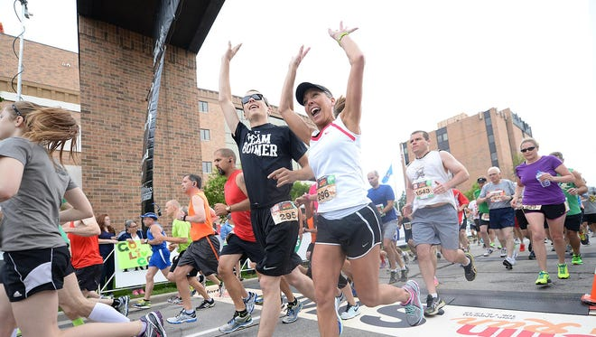 Runners Drew Laubenstein of De Pere (295) and Cheryl van Straten (296) cheer as they start the 2015 Bellin Run.
