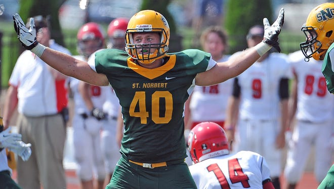 St. Norbert College linebacker R.J. Callow (40) celebrates his sack of quarterback Nick Anzelmo (14) against Carthage College on Sept. 5. Callow leads the Green Knights with 64 tackles this season.