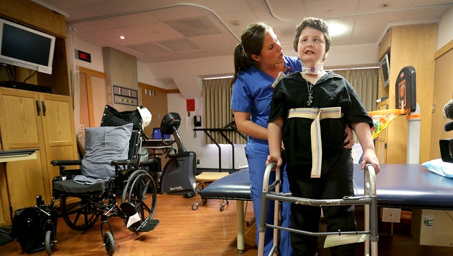 John Rogers works with physical therapist Angela Keyler at  Riley Hospital for Children.
