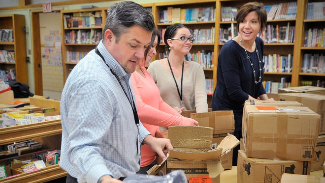 Staff at Lincoln Elementary School unpack boxes of hats and mittens for students on Tuesday, Dec. 8. The Rotary Club of St. Cloud donated the winter gear to students.