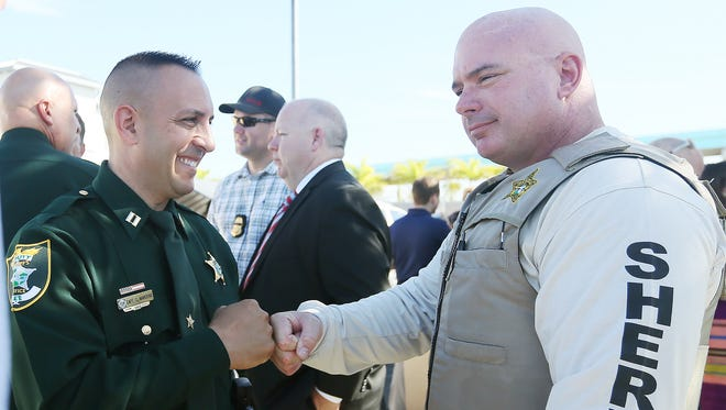 Capt. Carmine Marceno of the Lee County Sheriff's Office, left, congratulates Lt. Christopher Nyce, of the Sheriff's Office Marine Unit, on Sunday for helping capture three suspects in a recent boat theft that spanned more than 300 nautical miles. Details of the capture were given at a press conference at the U.S. Coast Guard Station on Fort Myers Beach.