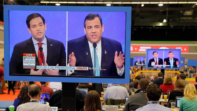 Marco Rubio and Chris Christie are seen on press room television monitors during the GOP debate at Saint Anselm College in Manchester, N.H. on Feb. 6, 2016.