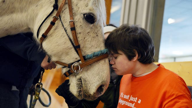 """After a 20-minute ride, Danielle Hake, 18, has """"snuggle time"""" with her therapy horse Edgar at Leg Up Farm in East Manchester Township on Friday, Dec. 20, 2013. Most horse therapy clients help brush their horses after their ride, but because of her extreme special needs, Danielle nuzzles the horse afterwards instead. Danielle Hake of Newberry Township suffers from chronic static encephalopathy, severe autism, focal epilepsy and abnormal thermoregulation. Although she is 18 years old, she functions mentally at a toddler level and is nonverbal. Because of her extreme special needs, she is unable to sweat and cannot be exposed to extreme heat or cold. Danielle's parents, Alan Hake and Tina Leese, have constantly adapted to meet their daughter's needs, but they are unsure who will provide Danielle with the 24-hour care she requires after they are gone."""