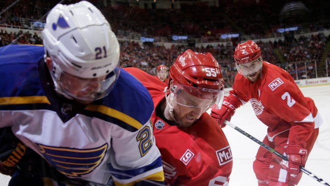 """The Blues' Patrik Berglund gets jammed against the boards as the Red Wings' Niklas Kronwall fights for a loose puck and Brendan Smith looks on in the second period. The Wings celebrated the life of owner Mike Ilitch with a """"Mr. I"""" patch on their left shoulder Wednesday, Feb. 15, 2017 at Joe Louis Arena."""