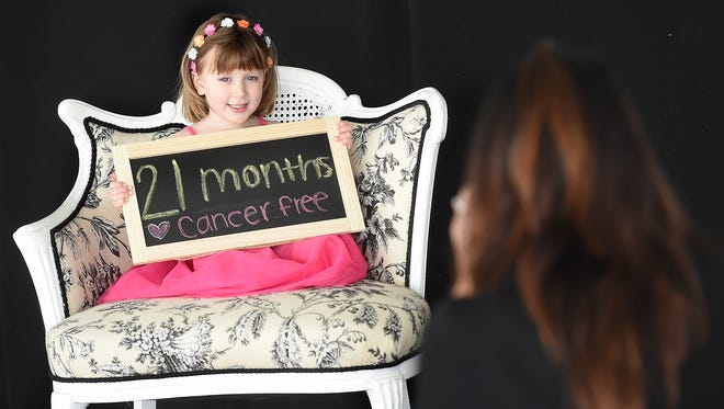 Sarah Zeisloft holds up a sign indicating how long she has been in remission from cancer. The 4-year-old from Lebanon County was having her photos taken by Julie Albright, one of the photographers who volunteered for the two-day photo shoot at Lauxmont Farms in Lower Windsor Township.