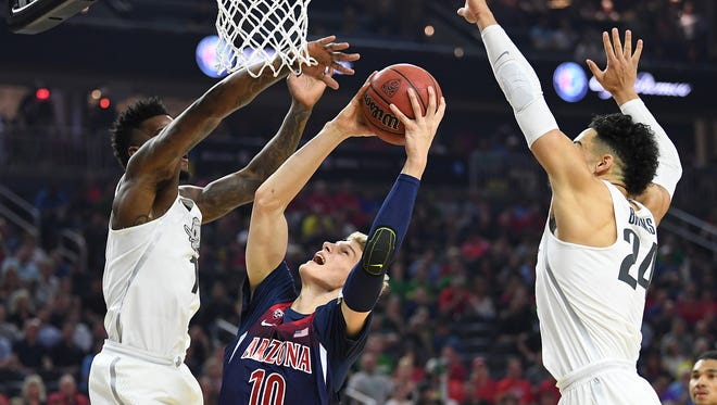 Mar 11, 2017; Las Vegas, NV, USA; Arizona Wildcats forward Lauri Markkanen (10) shoots between Oregon Ducks defenders during the Pac-12 Conference Championship game at T-Mobile Arena. Mandatory Credit: Stephen R. Sylvanie-USA TODAY Sports
