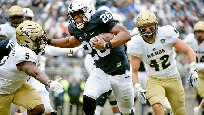 Penn State's Saquon Barkley rushes for a touchdown against Akron's Ulysees Gilbert III in the first half of an NCAA Division I college football game Saturday, Sept. 2, 2017, at Beaver Stadium. Penn State, fresh off a Big 10 Championship win, shut out Akron 52-0 in its season opener.