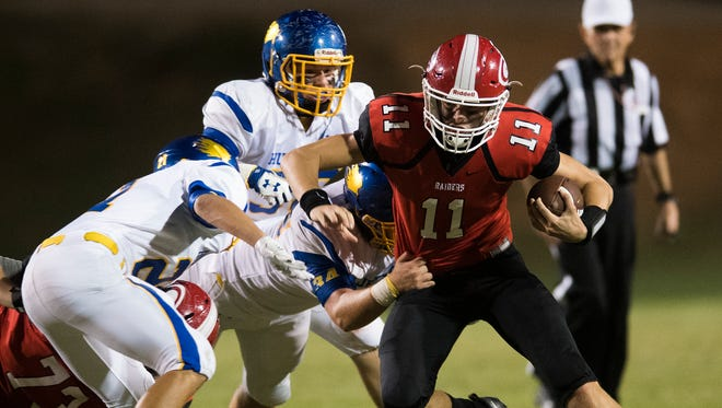 Greenville's Davis Beville (11) attempts to evade Wren's defense during the Red Raiders' 46-14 victory Friday night at Sirrine Stadium.