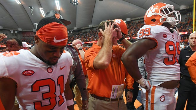 Clemson head coach Dabo Swinney, center, along with defensive back Ryan Carter (31), left, and defensive lineman Clelin Ferrell (99) leave the field after the Tiger's 27-24 loss to Syracuse on Friday, Oct. 13, 2017 at the Carrier Dome in Syracuse, N.Y.