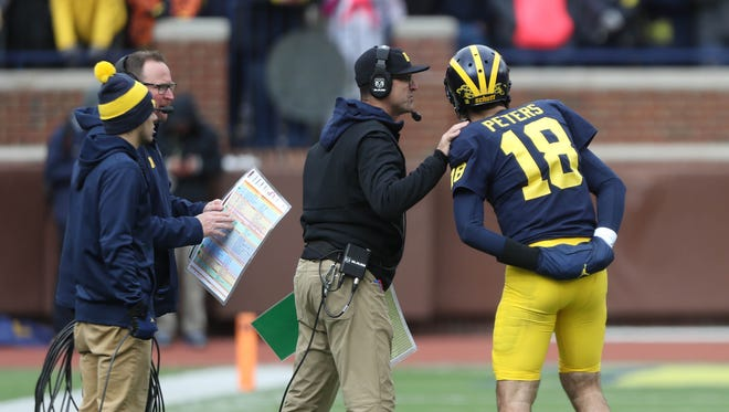 Jim Harbaugh talks with Brandon Peters in the fourth quarter of Michigan's 35-14 win over Rutgers, Saturday, Oct. 28, 2017 at Michigan Stadium.