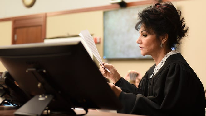 Circuit Judge Rosemarie Aquilina looks at a letter from Larry Nassar Thursday, Jan. 18, 2018, in her  courtroom before the third day of victim impact statements.