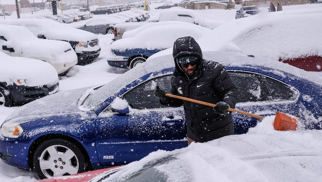 Michigan law requires motorists to clean snow off their vehicles or risk a ticket.