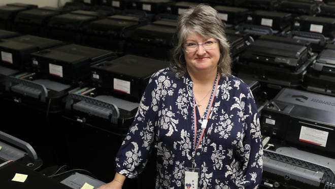 Shasta County Clerk and Registrar of Voters Cathy Darling Allen stands among some of the 95 new ballot machines that the county has recieved.