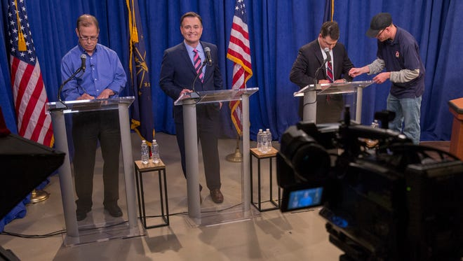 Mike Braun (left), Luke Messer, and Todd Rokita get their microphones, proir to a debate of Indiana Republican candidates for Senate, at WISH TV, Indianapolis, Sunday, April 15, 2018.
