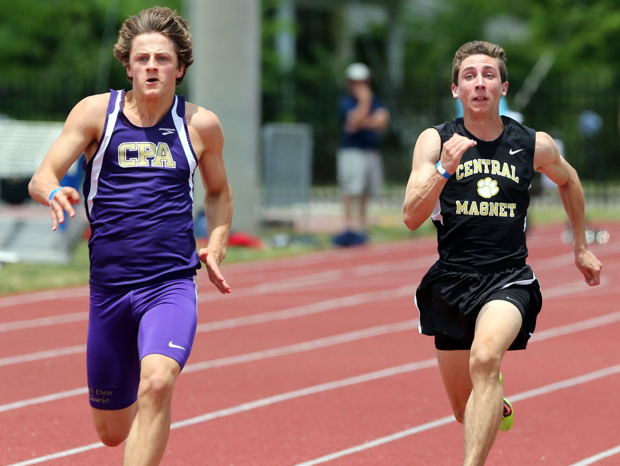 CPA's William Stout, left, and Central Magnet's Ben Waldecker run in the 100-meter dash during the Class A/AA decathlon. Stout took first place.