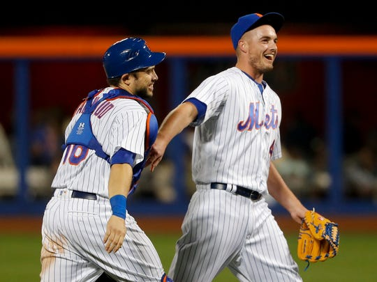 New York Mets catcher Travis d'Arnaud, left, and pitcher Addison Reed walk off the field after the Mets defeated the Philadelphia Phillies 2-1 in a baseball game, Friday, June 30, 2017, in New York.