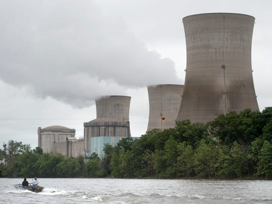 A boat makes its way past the towers of Three Mile Island in 2017. Three Mile Island will close in September 2019, following five years of losses, said plant owner Exelon Corp.