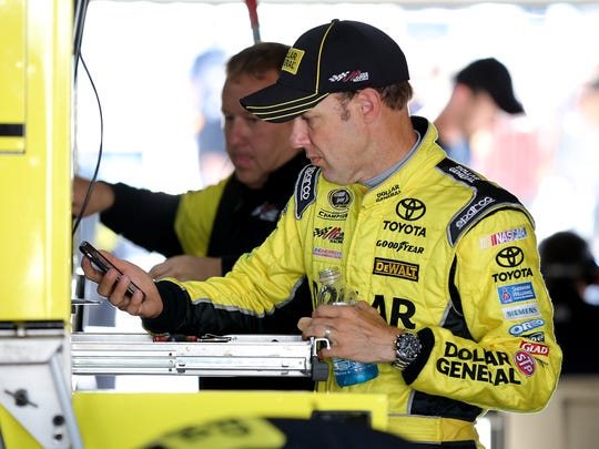 Matt Kenseth takes a moment to check his iPhone during the first practice for the Crown Royal Jeff Kyle 400 at the Brickyard Friday, July 24, 2015, morning at the Indianapolis Motor Speedway.