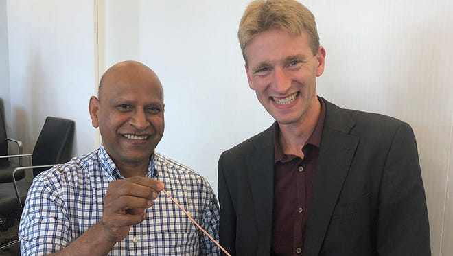 FAMU-FSU College of Engineering Professor and Associate Director of the Center for Advanced Power Systems Sastry Pamidi, left, and Danko van der Laan, CEO of Advanced Conductor Technologies, right, with a Conductor on Round Core (CORC) cable.