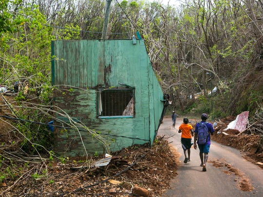 Villagers of Calibishie, Dominica walk by a home that has fallen on it's side resting on the main road cause by Hurricane Maria.