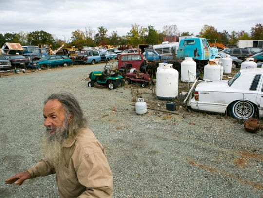 Vincent DellAversano, owner of land where the former Delaware Sand and Gravel Landfill sat, walks around his salvage yard.