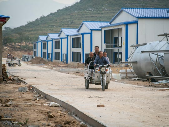 Local farmers drive by the Huayu Group's new breeding facilities in the mountains of the Hebei province.