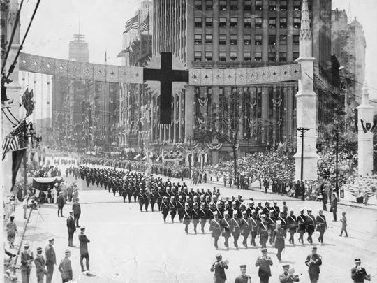 The Knights Templar march on Woodward Avenue in 1928, under the symbol of the red cross.