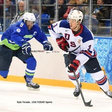USA defenseman Cam Fowler (3) skates with the puck past Slovenia forward Tomz Razingar (9).