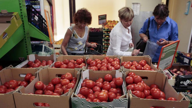 Women choose Dutch tomatoes at a supermarket in downtown Moscow. The Russian government has banned all imports of meat, fish, milk and milk products, and fruit and vegetables from the United States, the European Union, Australia, Canada and Norway.
