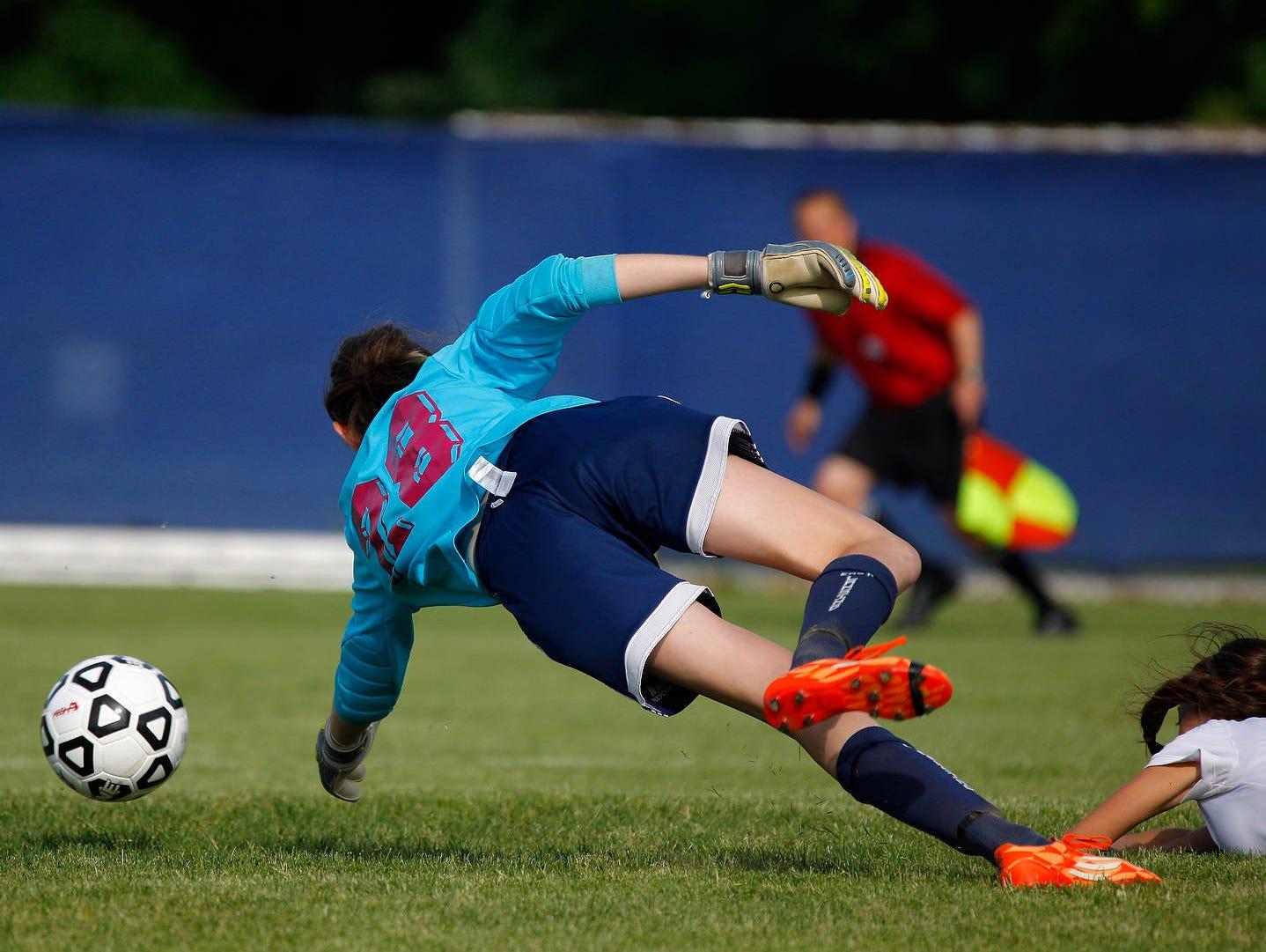 St. Johns' Lexi McPherson, right, gets the ball past East Lansing goalkeeper Madeline Chomentowski for St. Johns' first goal Thursday, June 2, 2016, at DeWitt High School. St. Johns won 4-0.