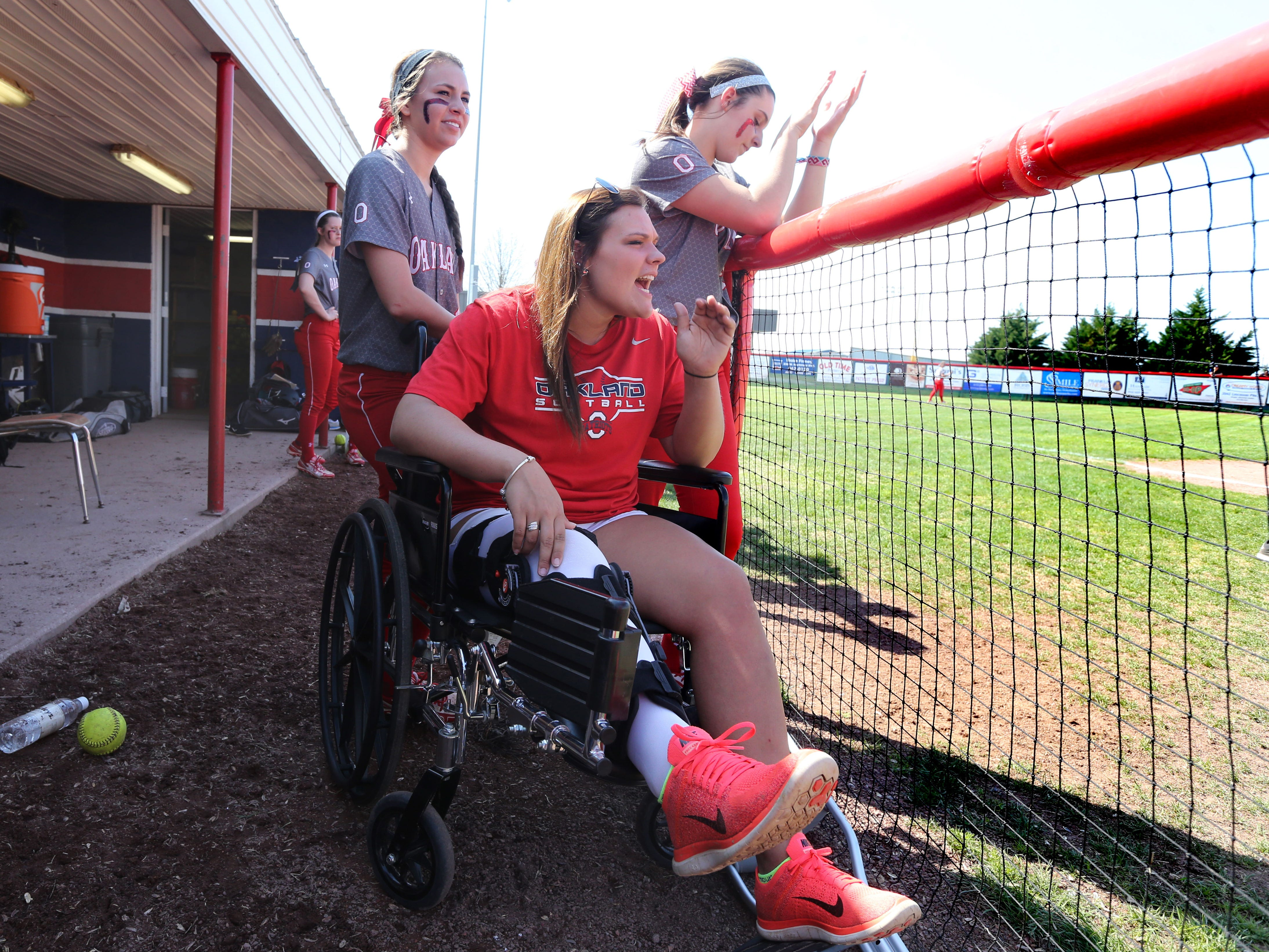 Oakland's Savannah Lee cheers on her team from a weelchair in the dugout. Lee suffered a season-ending knee injury last month.Oakland's Maddy Constantinescu, left and Maleia Gray, right stand behind Lee.