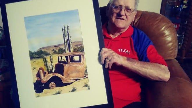 "Chuck Markham holding his painting, ""Desert Yard Art."""