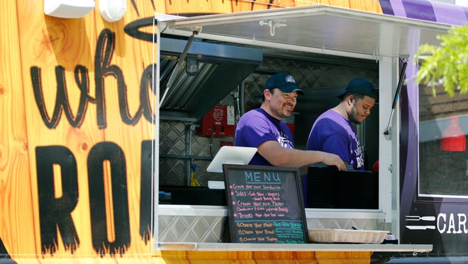 Owner of Whole-E Roasters food truck Chris Marmo and Kenny Jackson prepare lunches in this file photo.