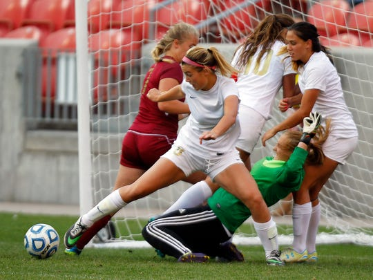 Logan and Cedar fight to control the ball in front of the Cedar goal in the 3A girls high school soccer championship at Rio Tinto Stadium on Saturday.