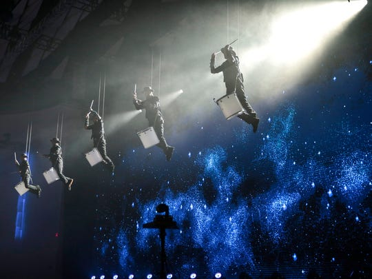 Drummers suspended from the ceiling perform before