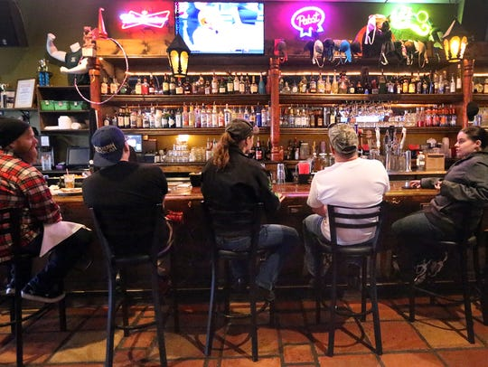 Patrons sit at the bar to eat and drink while watching
