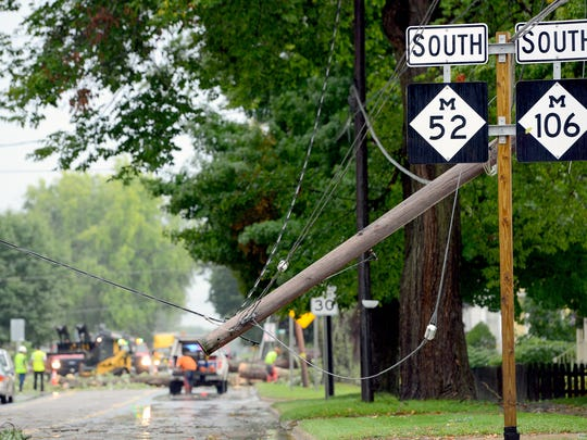 An utility pole hangs in the air as crews clean up a fallen tree near the intersection of Vernal and S. Clinton streets in Stockbridge Wednesday.