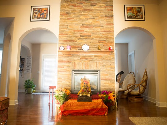 The fireplace of the Shibad home in Brentwood. On the walls hang photos of Sanskrit and Sankalp Shibad. On the fireplace stand statues of Lord Ganesha, in celebration of the Ganesha Festival.