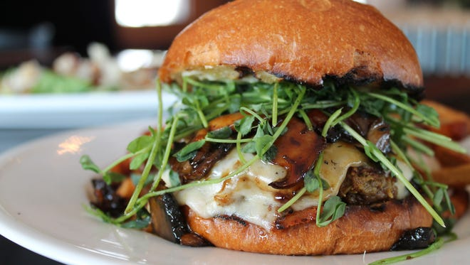 The Far East Burger is topped with soy honey mushrooms, Havarti cheese, pea shoots and roasted garlic mayo on brioche bun.