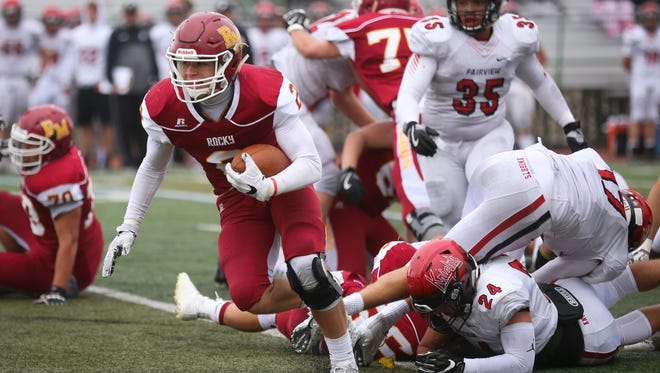 Rocky Mountain High School's Tyreese Adler breaks free from Fairview High School tacklers on Saturday in Fort Collins.