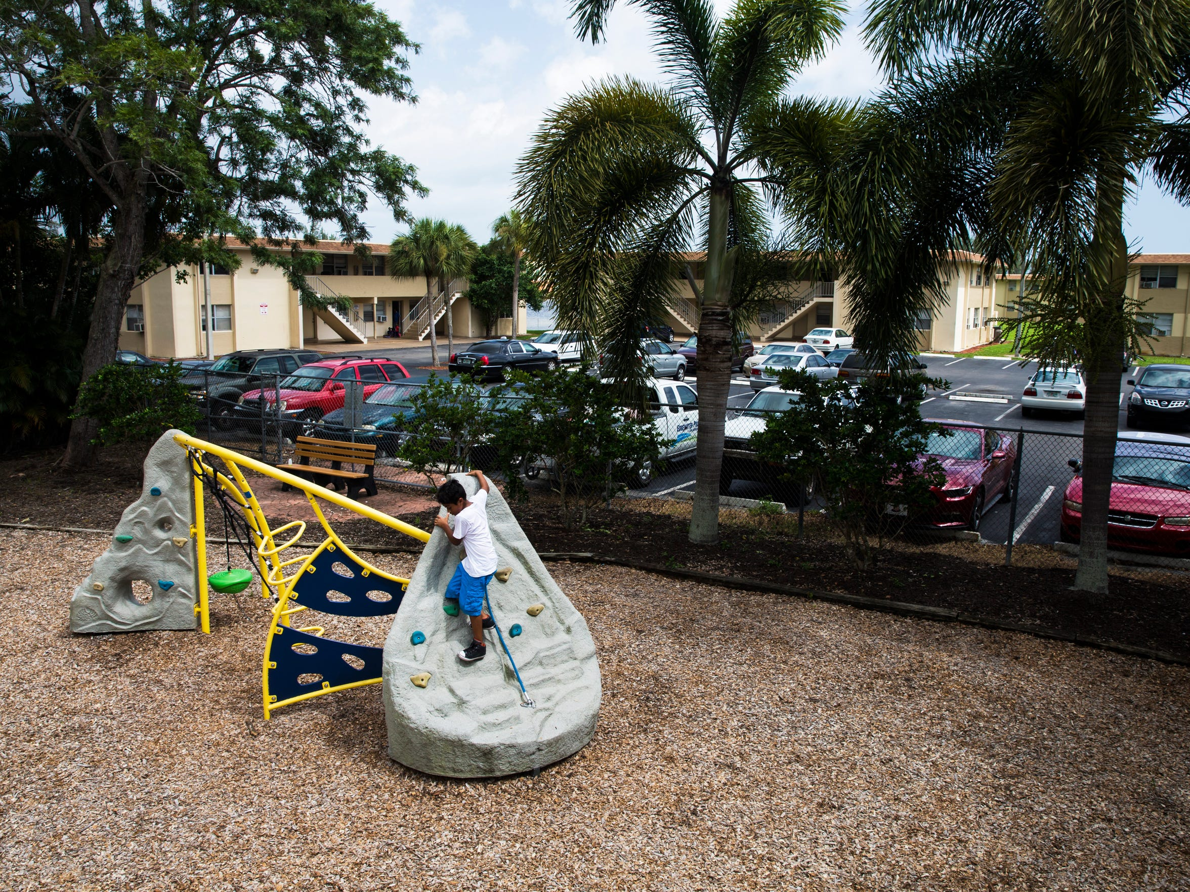 "A young boy climbs the jungle gym at the Anthony Park playground on Saturday, Aug. 5, 2017. The park has neighbored the Gordon River Apartments, a 96-unit housing project, for decades. ""If all those apartments were condominiums, and all the white folks were in there, they probably would have built a nice Baker Park here, and all the amenities that go with it,"" Willie Anthony said."