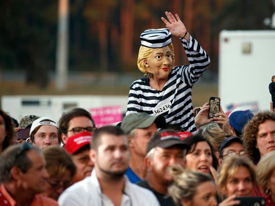 Supporters of Republican presidential candidate Donald Trump listen to him speak during a campaign rally, Tuesday, Oct. 25, 2016, in Tallahassee, Fla. Russians hired people to show up at similar rallies dressed in a costume similar to this Hillary Clinton outfit in prison garb. (AP Photo/ Evan Vucci)